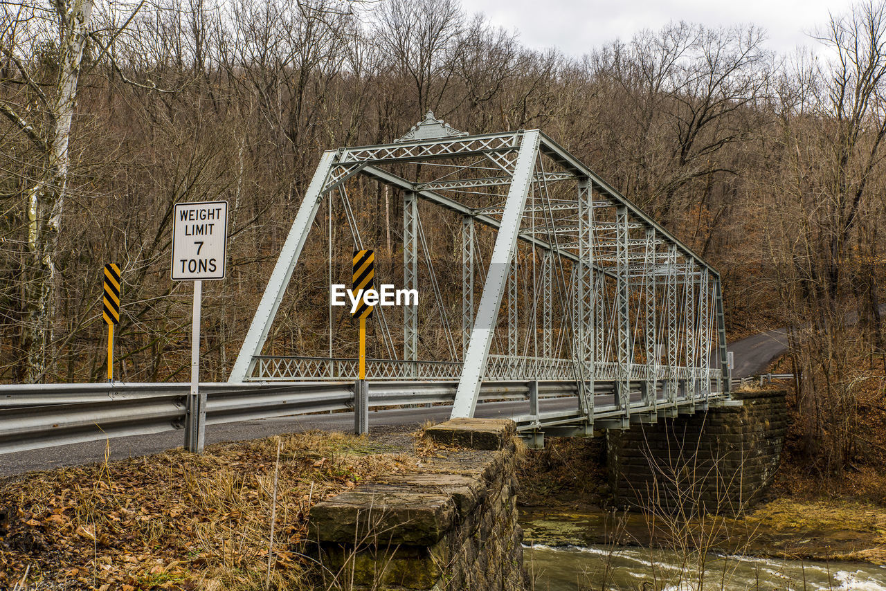 tree, architecture, built structure, plant, water, nature, no people, day, bare tree, bridge, river, bridge - man made structure, railing, sky, land, text, tranquility, sign, outdoors