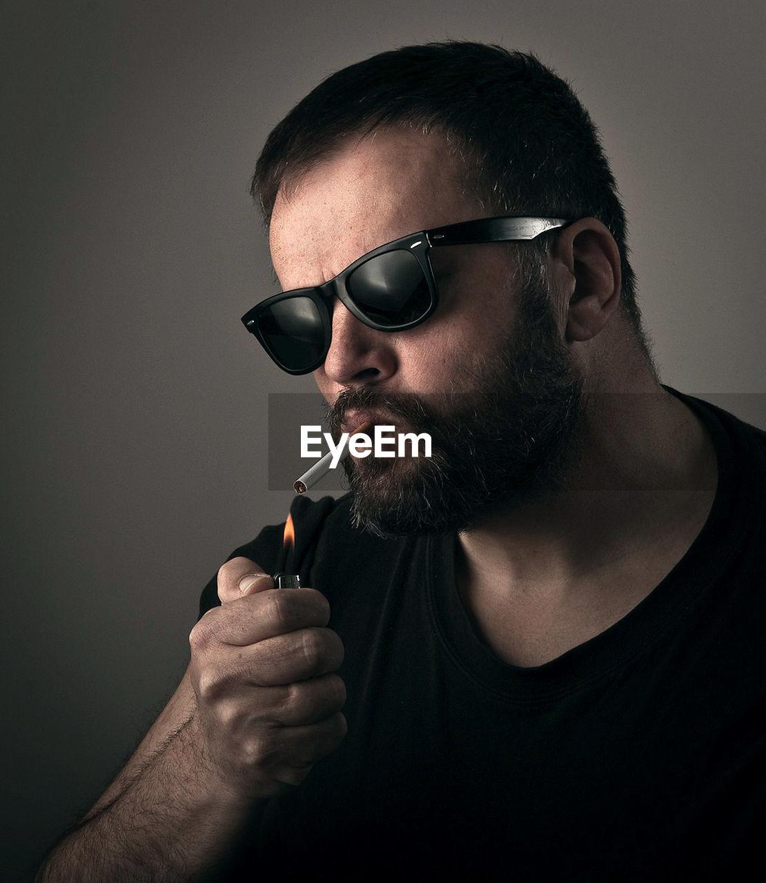 Close-Up Portrait Of Man Lighting Cigarette