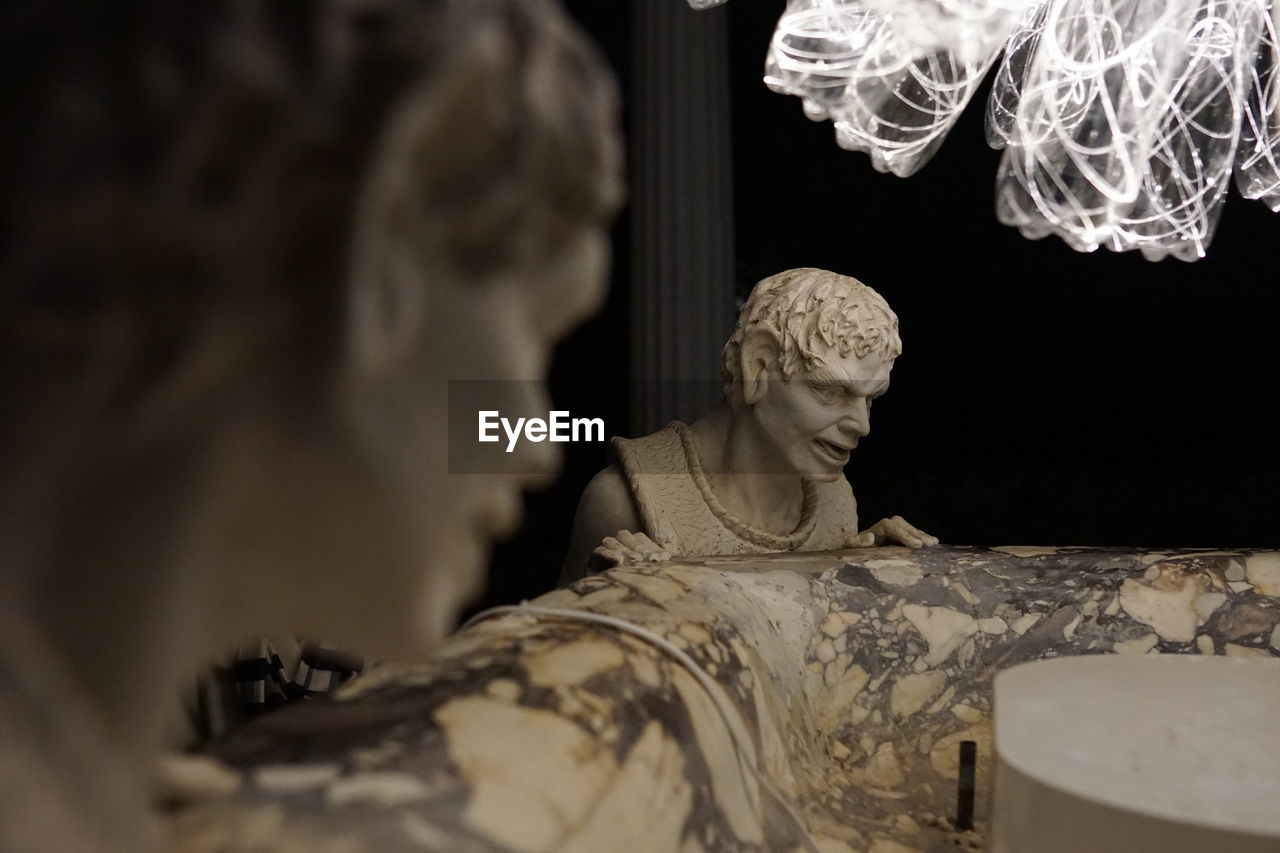 human representation, sculpture, art and craft, representation, statue, creativity, male likeness, indoors, architecture, no people, selective focus, craft, female likeness, built structure, low angle view, history, the past, night, lighting equipment, angel