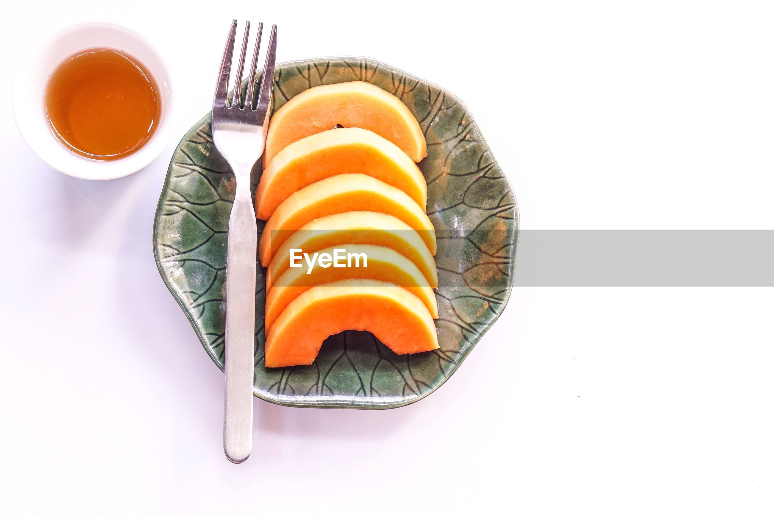 High angle view of fruits in plate on white background