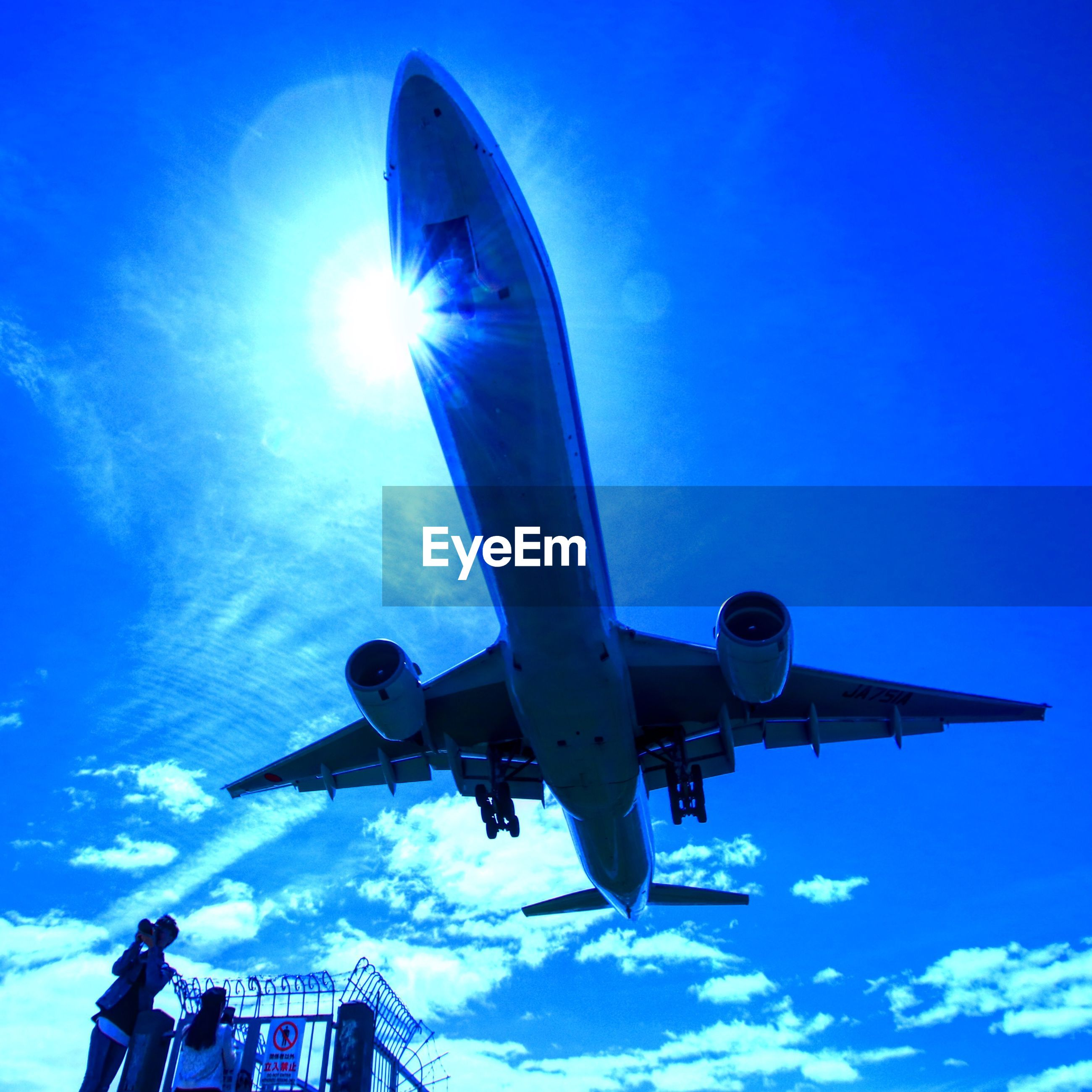 sky, air vehicle, blue, low angle view, mode of transportation, airplane, nature, transportation, sunlight, cloud - sky, motion, flying, travel, day, on the move, sun, outdoors, mid-air, sunbeam, no people, lens flare, aerospace industry, plane
