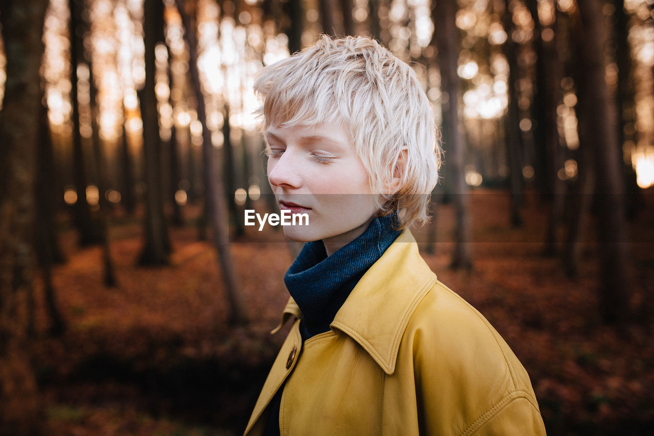 focus on foreground, one person, jacket, blond hair, autumn, outdoors, headshot, real people, lifestyles, tree, winter, warm clothing, portrait, day, young adult, nature, close-up, people