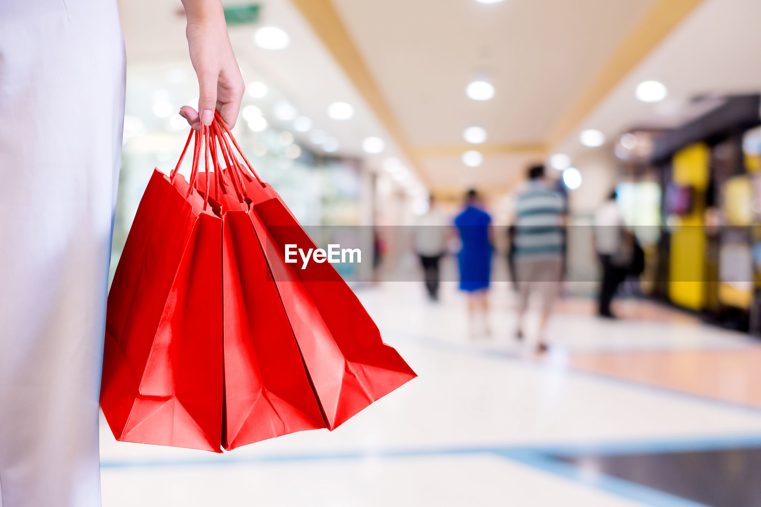 Midsection of woman holding red shopping bags at mall