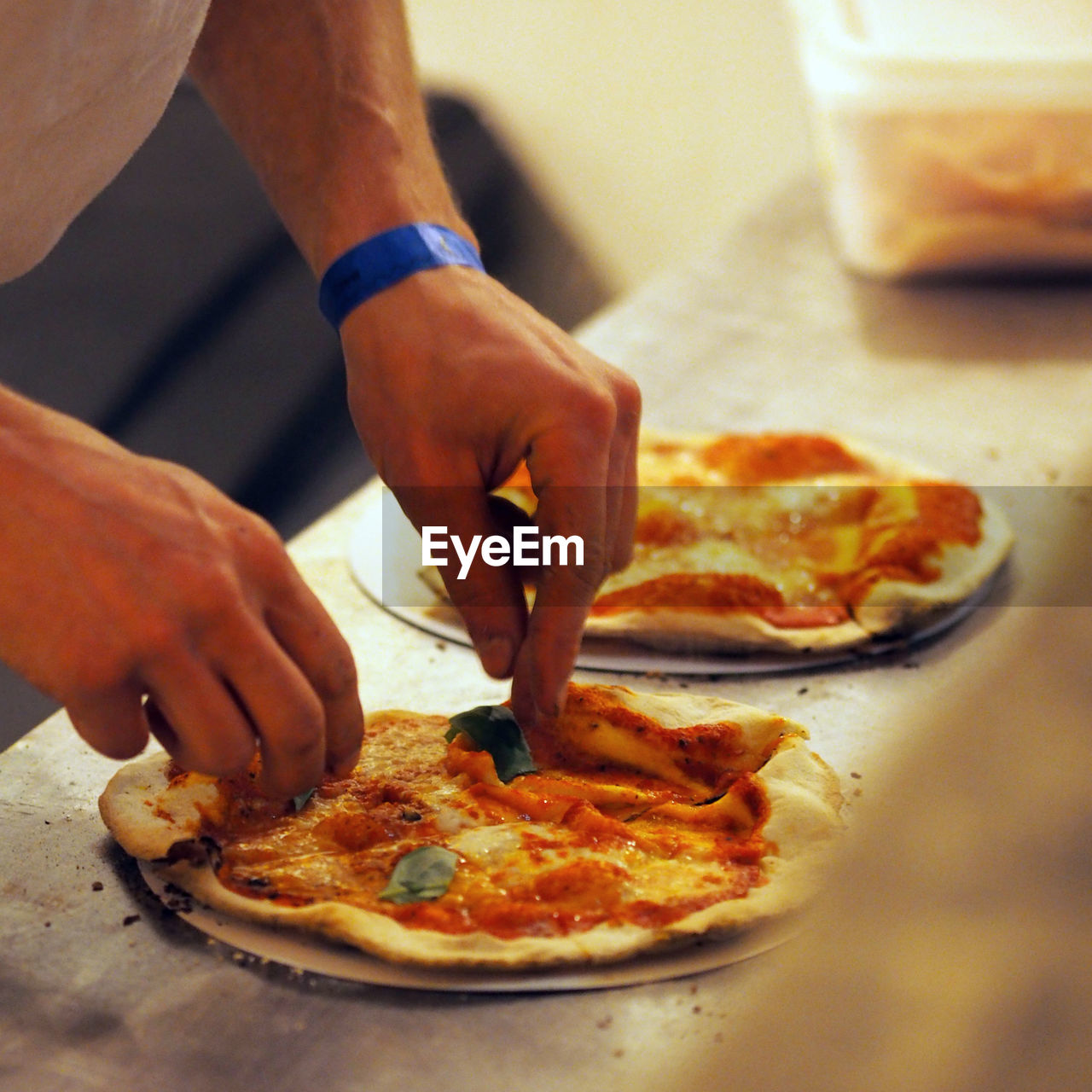 food and drink, food, pizza, human hand, hand, one person, indoors, freshness, unhealthy eating, table, human body part, real people, meal, holding, slice, men, cheese, ready-to-eat, business, preparing food, temptation, chef