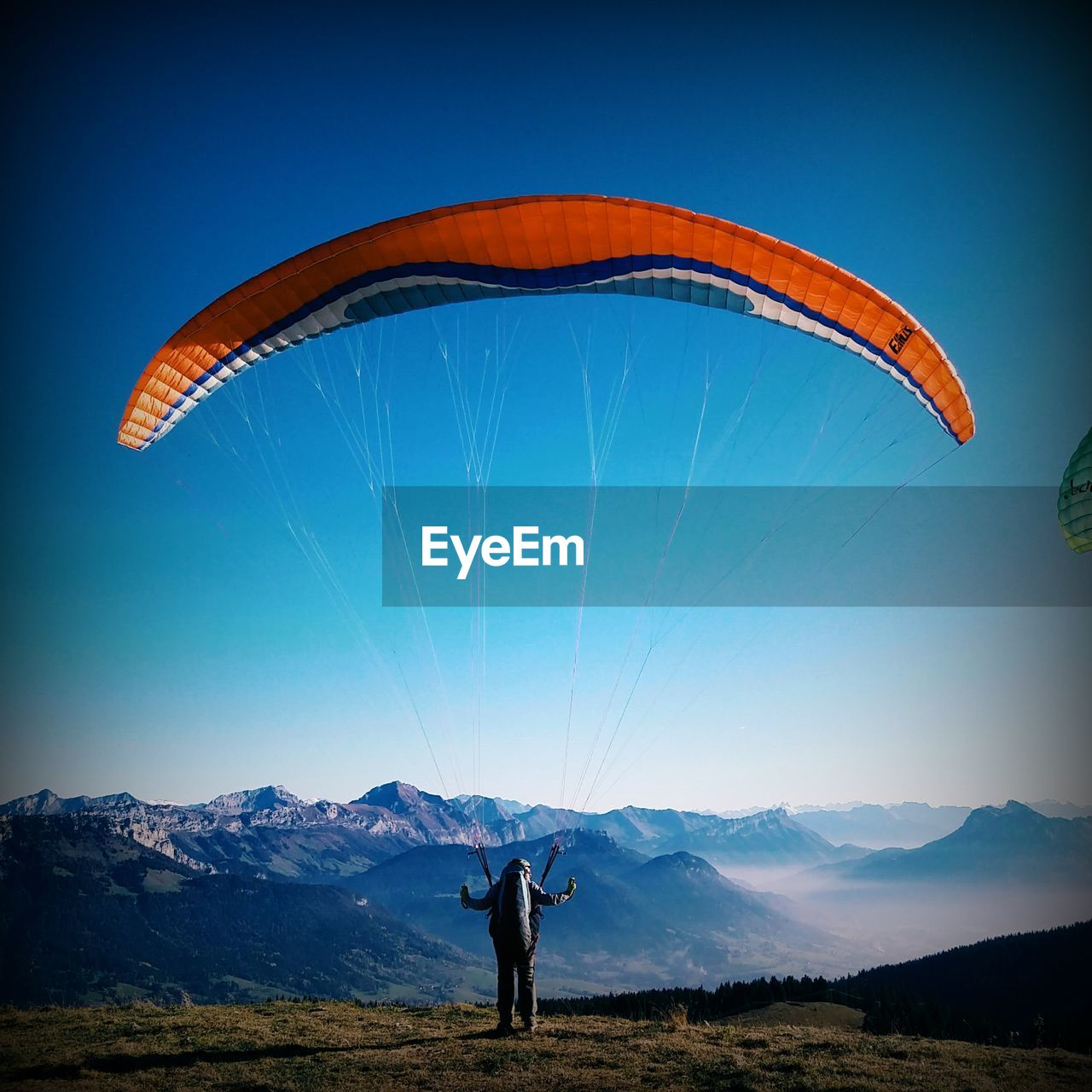 Rear View Of Paraglider Standing Against Mountain Range