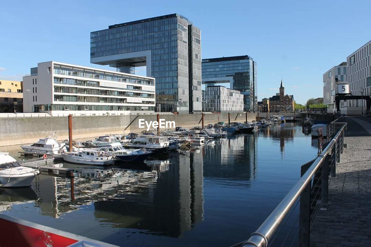 architecture, building exterior, built structure, water, reflection, nautical vessel, city, skyscraper, transportation, outdoors, waterfront, day, travel destinations, clear sky, sky, modern, moored, no people, nature