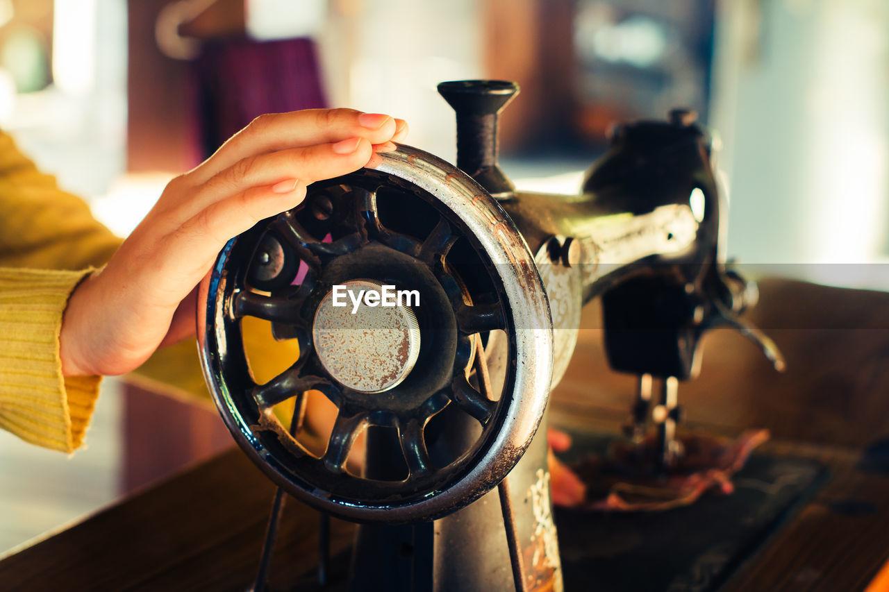 Close-up of women using sewing machine