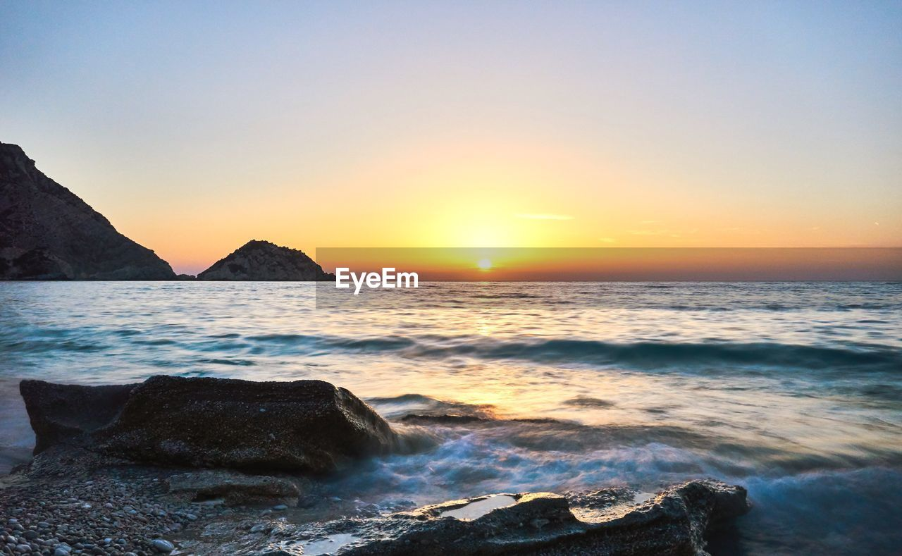 sea, water, sunset, sky, beauty in nature, scenics - nature, beach, horizon over water, horizon, motion, wave, land, sport, tranquility, idyllic, tranquil scene, clear sky, nature, rock, no people, sun, outdoors, power in nature