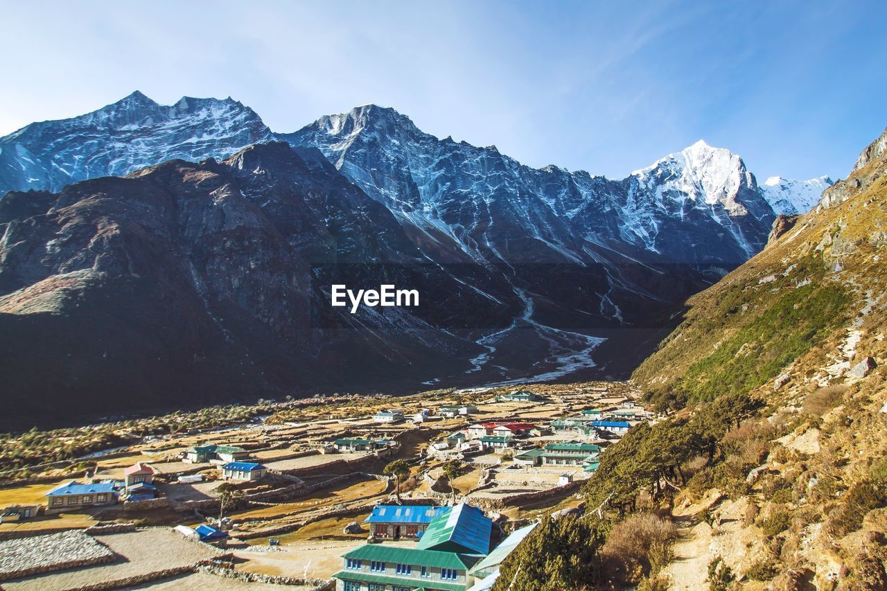 High angle view of village in valley against sky