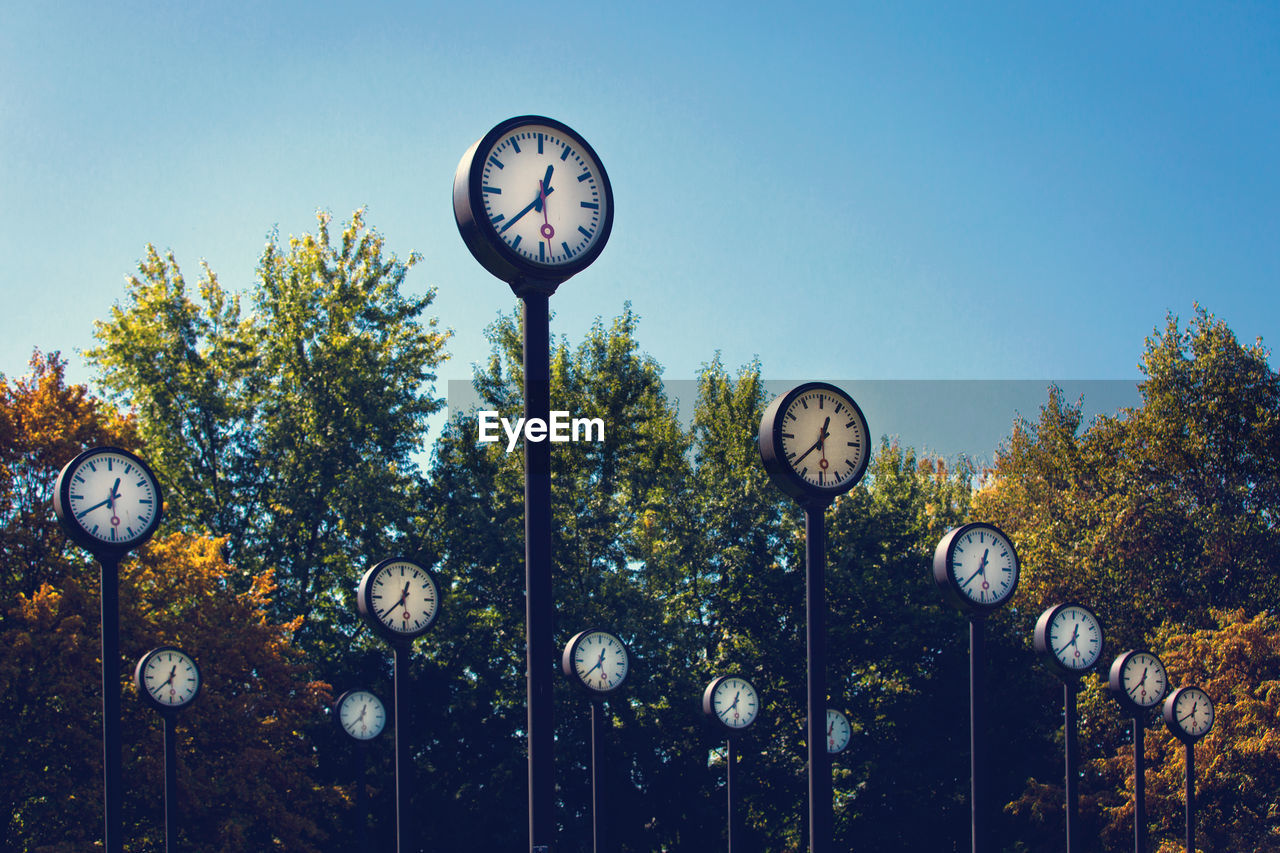 Low angle view of clocks and trees against clear sky