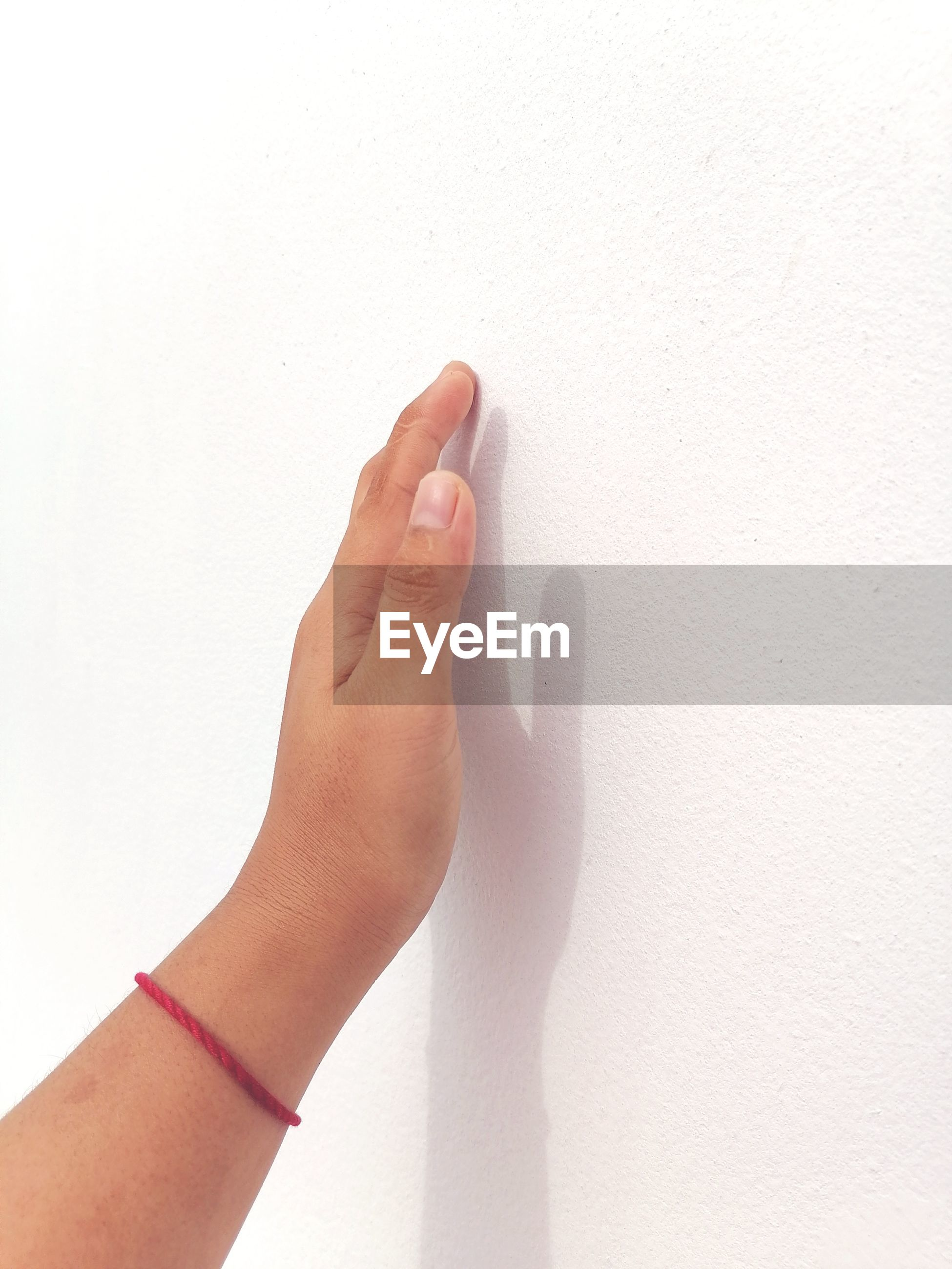 CLOSE-UP OF HANDS AGAINST WHITE WALL
