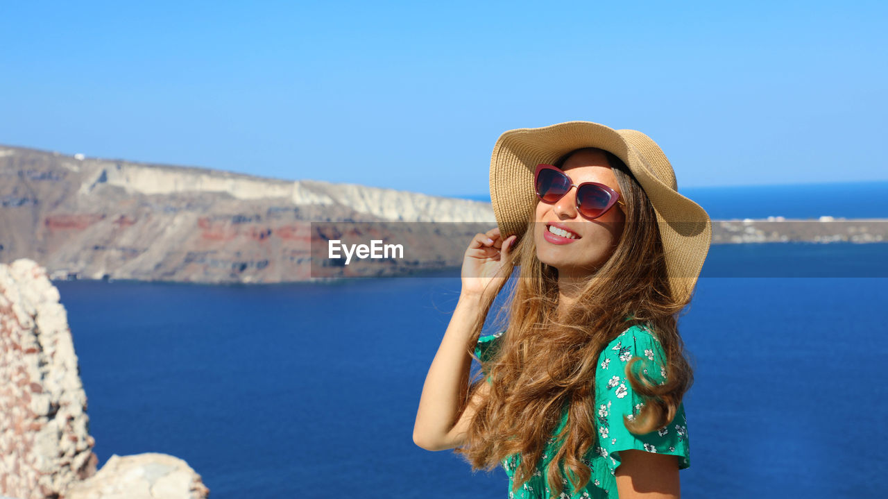 glasses, one person, sunglasses, water, long hair, young women, sea, young adult, leisure activity, fashion, hair, lifestyles, nature, sunlight, day, blue, real people, front view, standing, hairstyle, beautiful woman, outdoors, sun hat