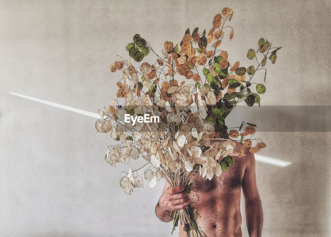 Shirtless man holding plant parts against wall