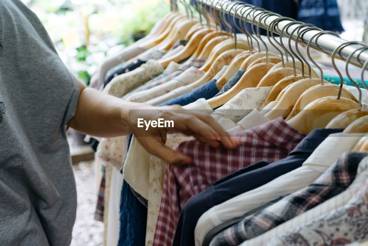 Midsection Of Woman Choosing Clothes From Rack In Store For Sale