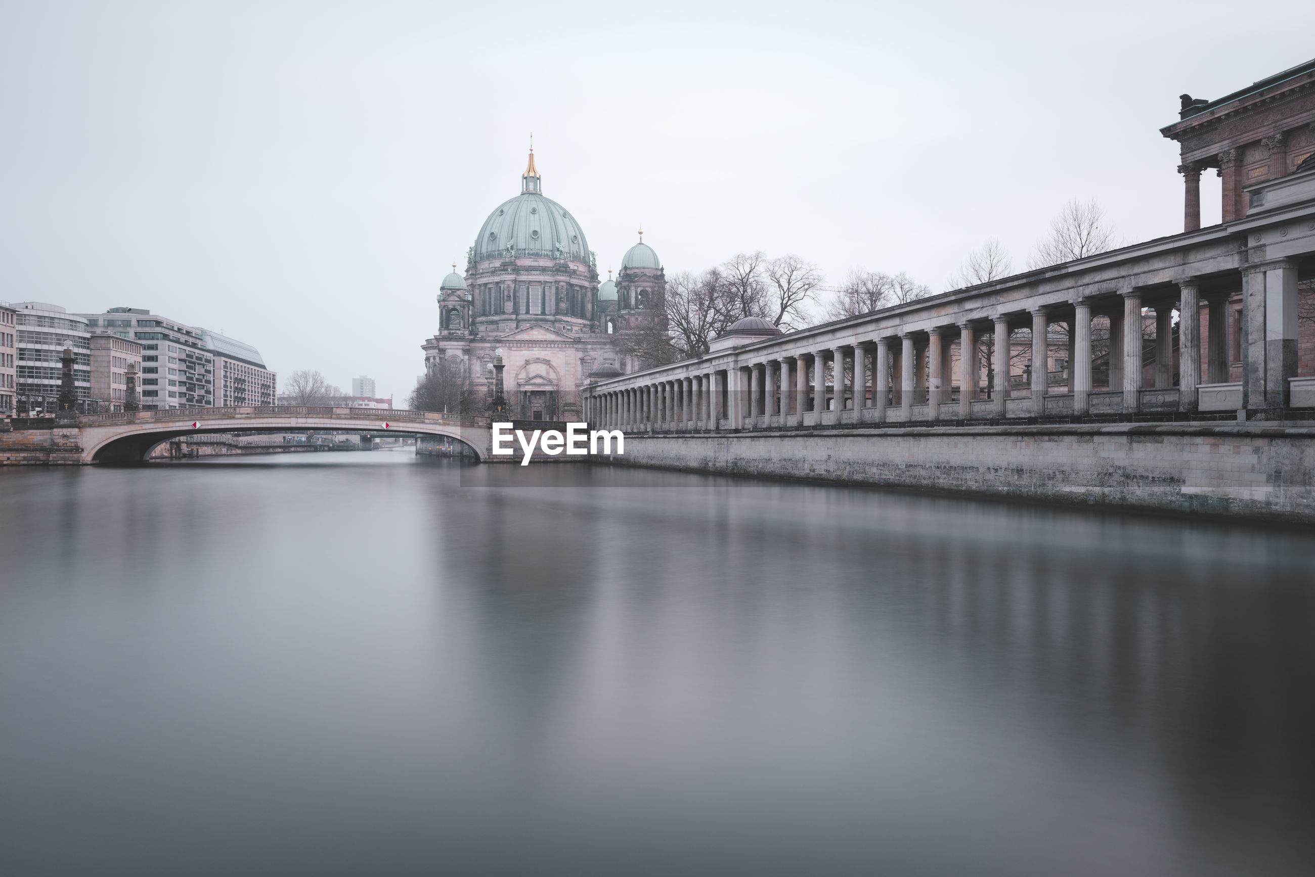 Bridge over spree river by berlin cathedral against sky in city