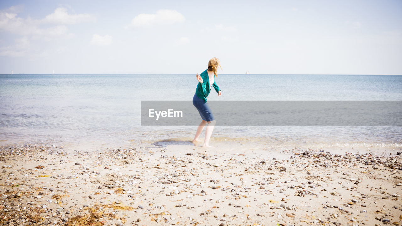 Full Length Of A Woman Standing On Beach Against Sky