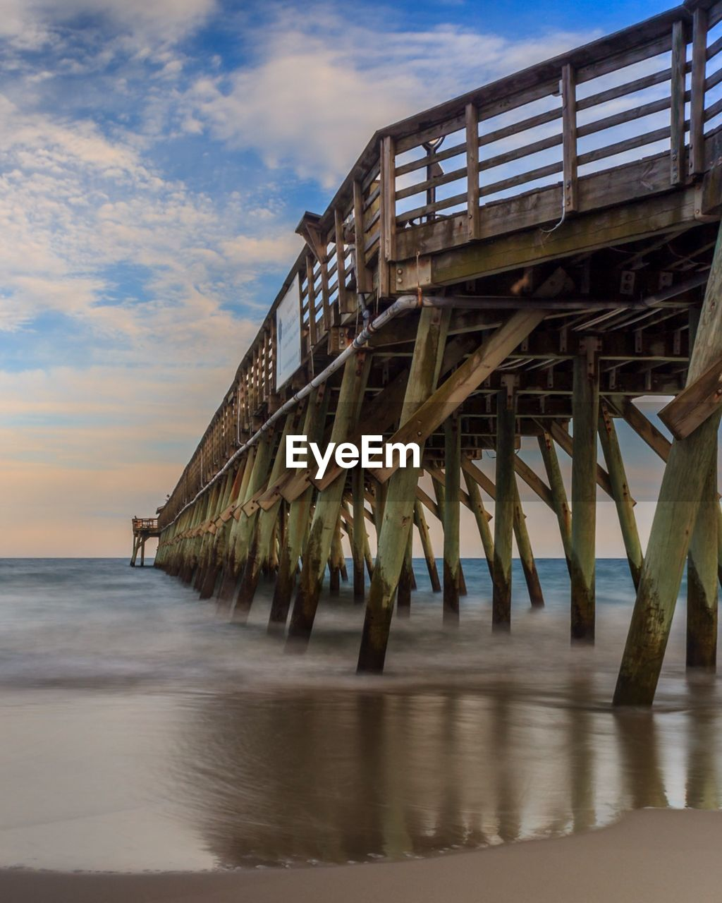 View Of Pier In Sea Against Cloudy Sky