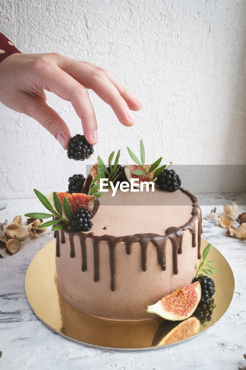 food and drink, food, human hand, sweet food, hand, human body part, sweet, dessert, indulgence, temptation, freshness, indoors, one person, cake, baked, unhealthy eating, real people, table, fruit, finger