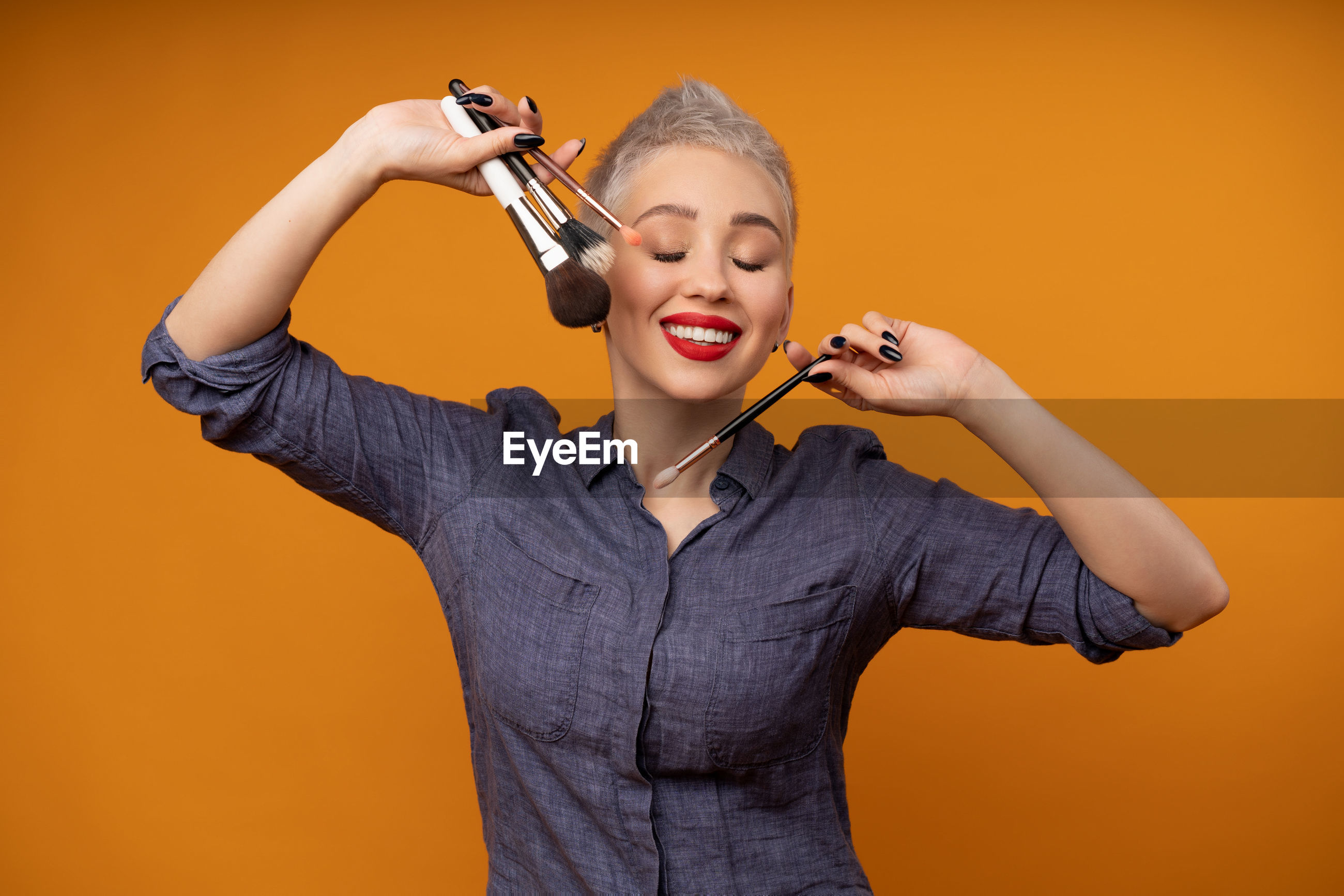 Smiling woman with make-up brush in mouth against orange background