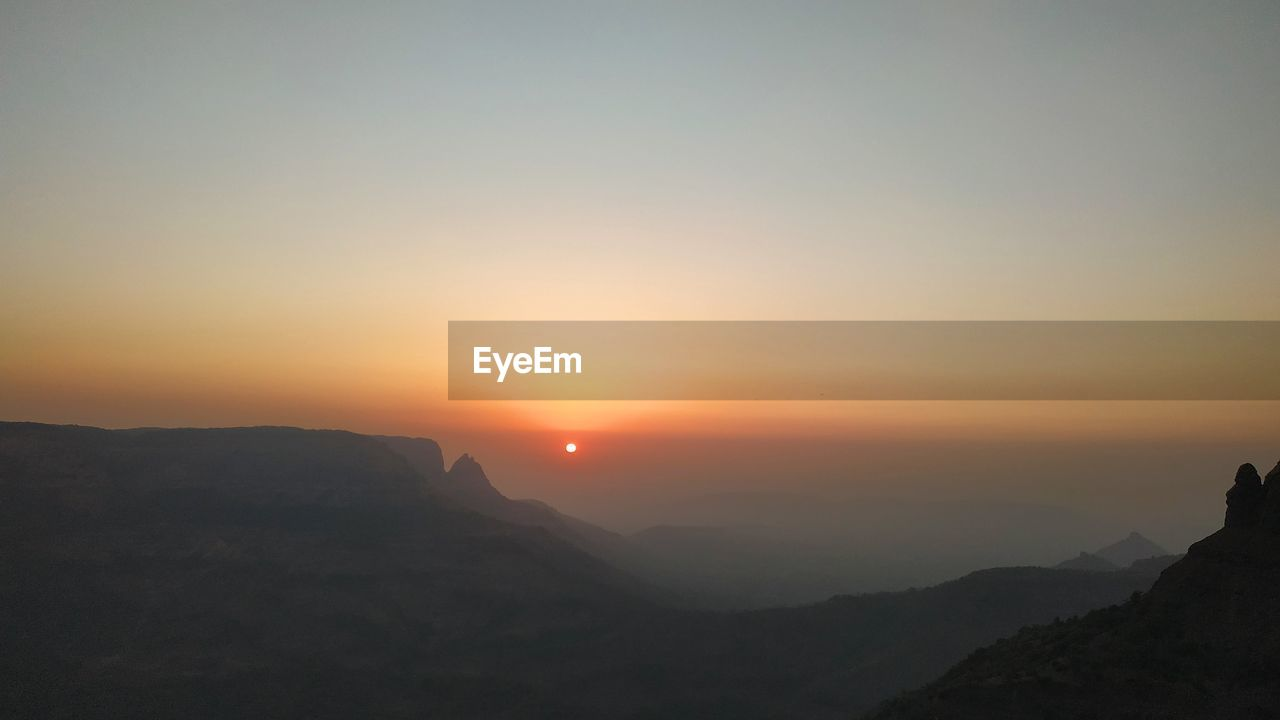 sky, mountain, sunset, beauty in nature, tranquility, tranquil scene, scenics - nature, nature, sun, idyllic, environment, mountain range, non-urban scene, orange color, silhouette, landscape, copy space, outdoors, no people, clear sky, mountain peak