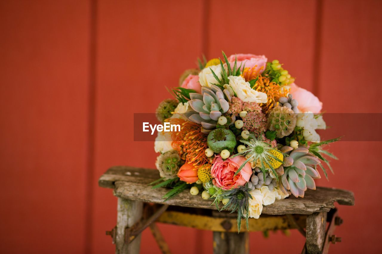 Close-up of bouquet on table against red wall