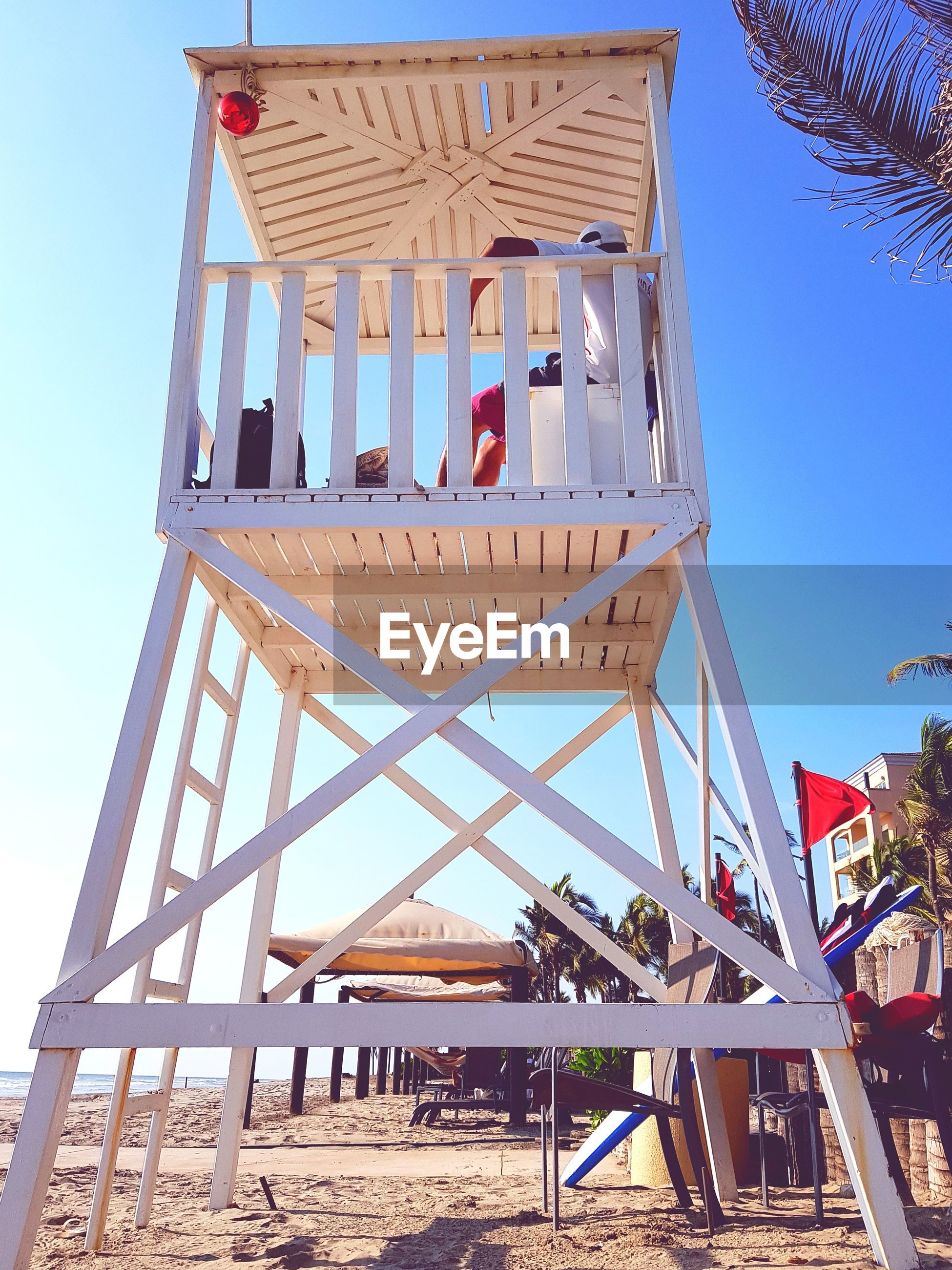 Low angle view of lifeguard sitting at beach