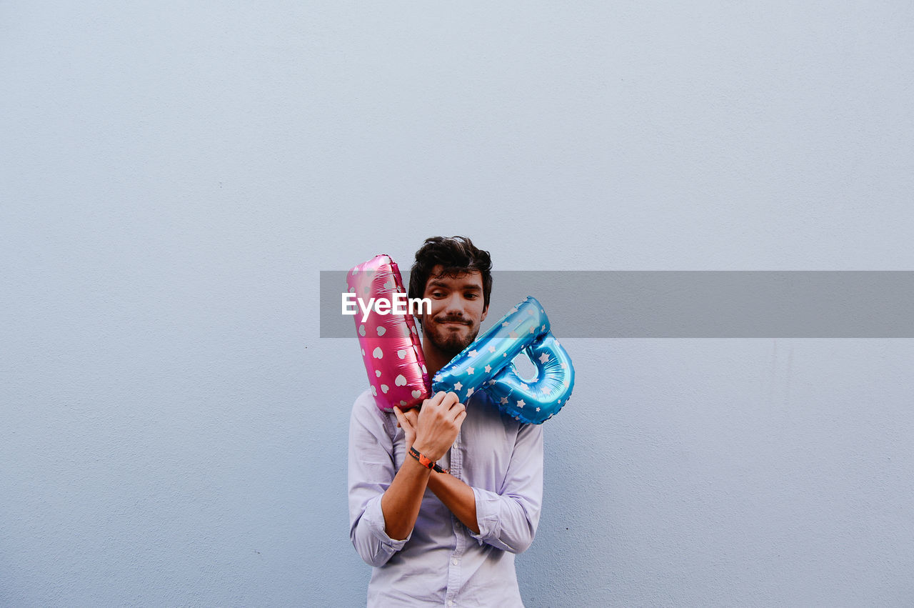 Portrait Of Young Adult Holding Balloons