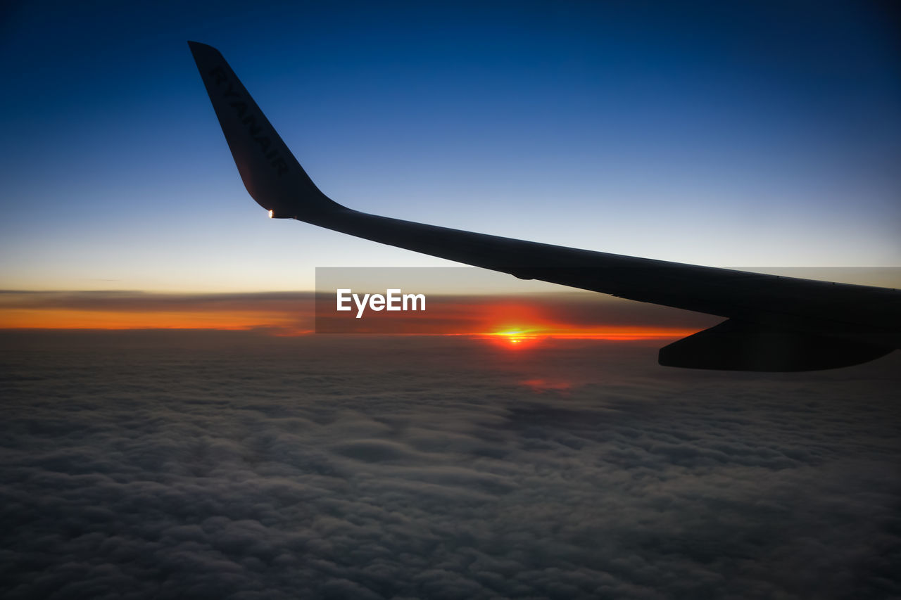 sky, air vehicle, sunset, airplane, mode of transportation, flying, sun, aircraft wing, transportation, mid-air, nature, beauty in nature, travel, scenics - nature, no people, cloud - sky, journey, public transportation, outdoors, on the move, aerospace industry