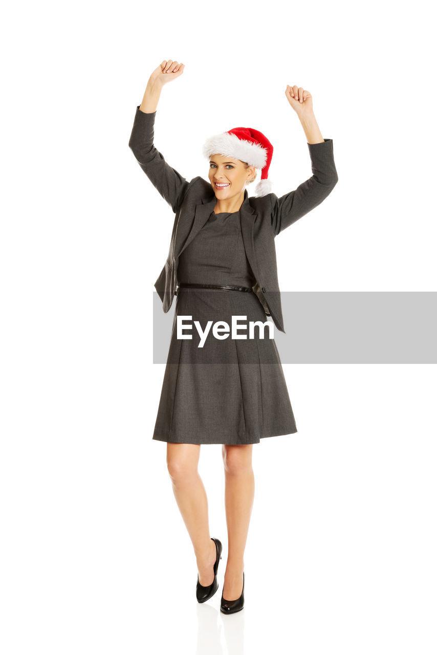 Portrait of cheerful businesswoman wearing santa hat against white background