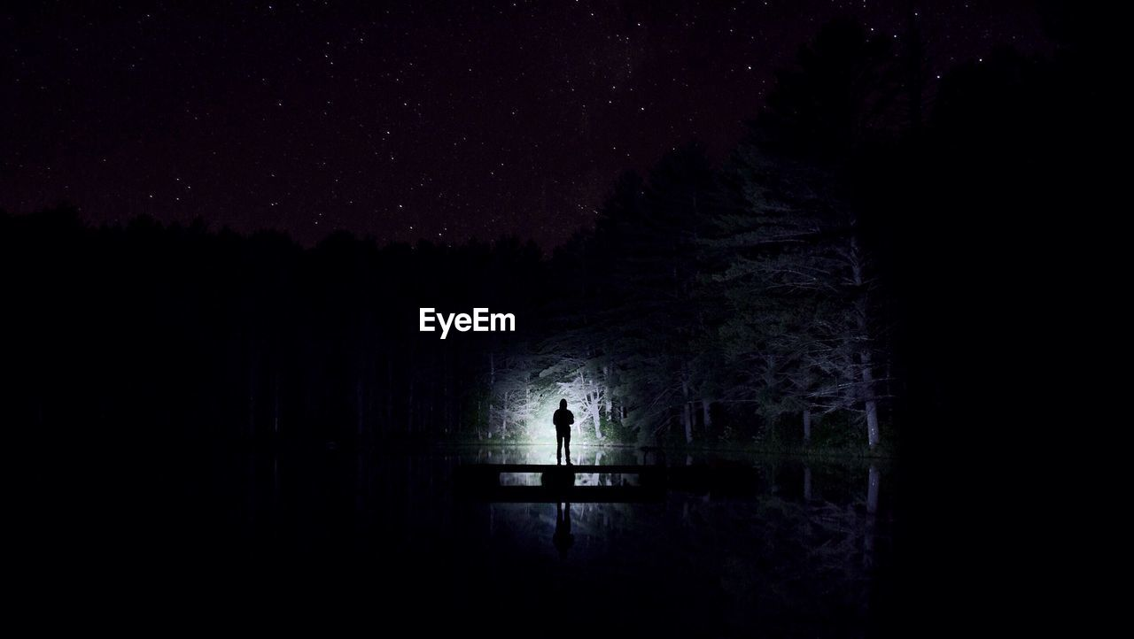 night, silhouette, tree, dark, one person, real people, standing, star - space, men, nature, beauty in nature, outdoors, sky, starry, water, astronomy, one man only, people