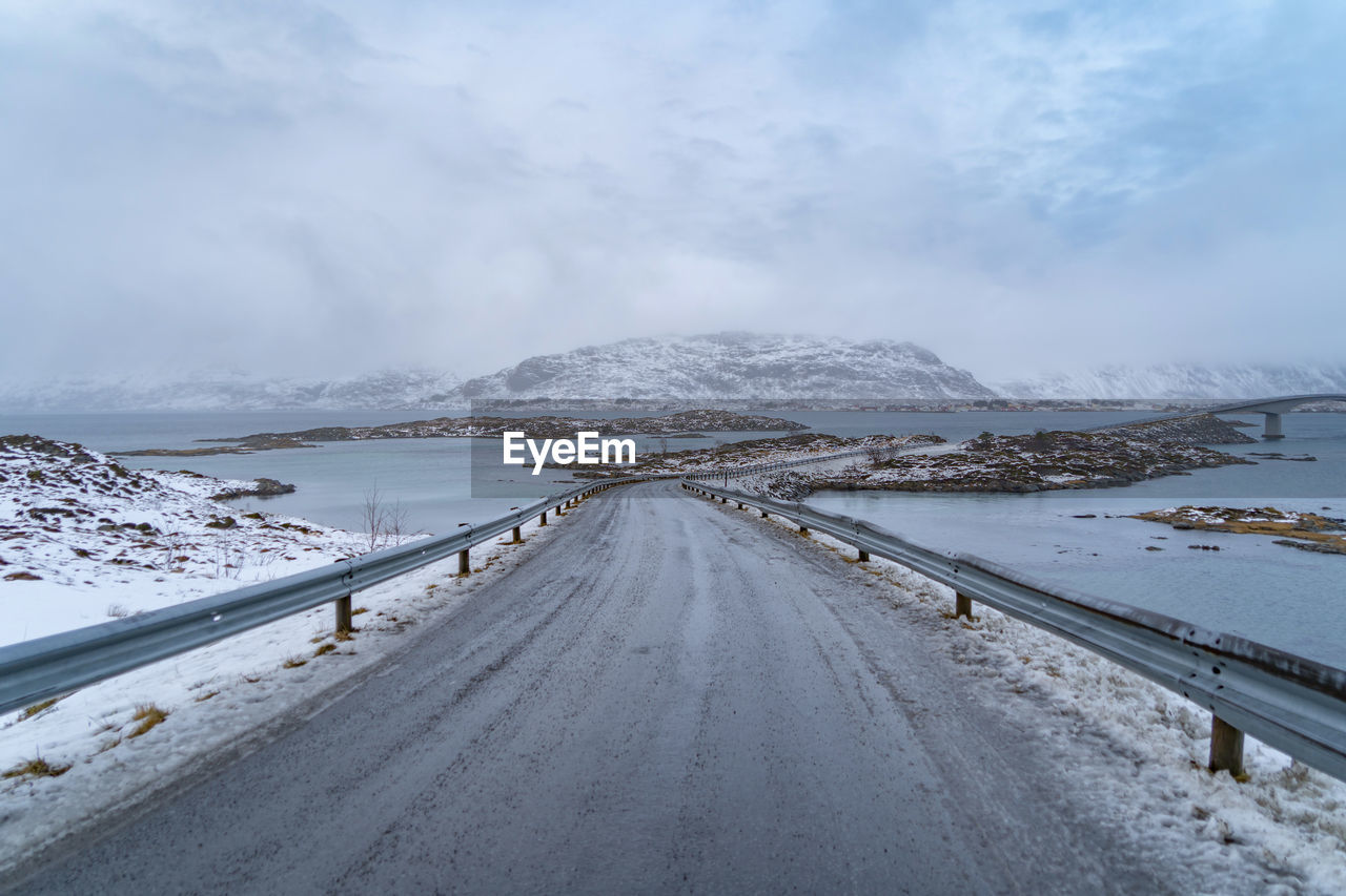 ROAD LEADING TOWARDS SNOW COVERED MOUNTAINS AGAINST SKY