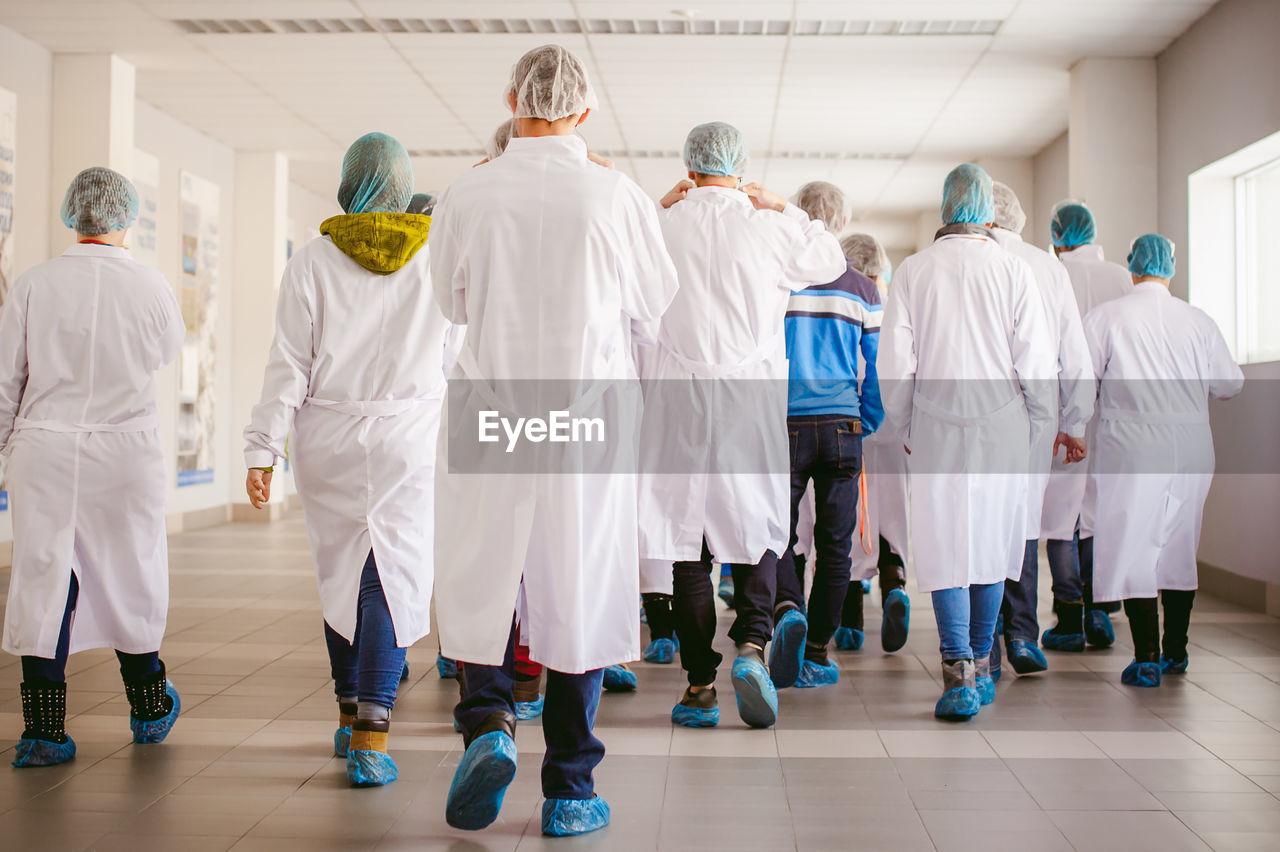Rear View Of Doctors Walking In Corridor