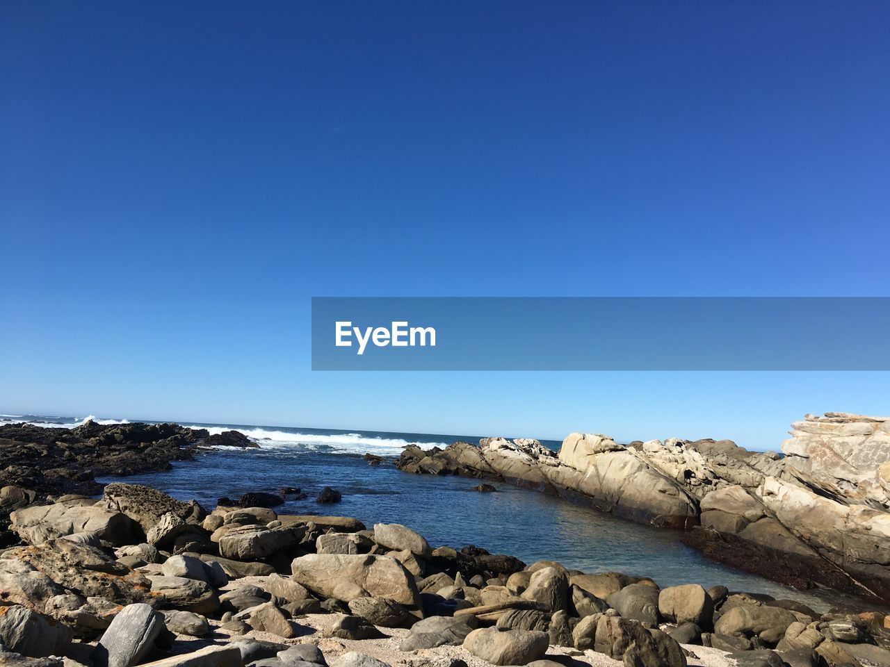 water, rock, sea, sky, blue, copy space, solid, rock - object, clear sky, beauty in nature, tranquility, nature, day, scenics - nature, tranquil scene, land, beach, no people, horizon, outdoors, rocky coastline