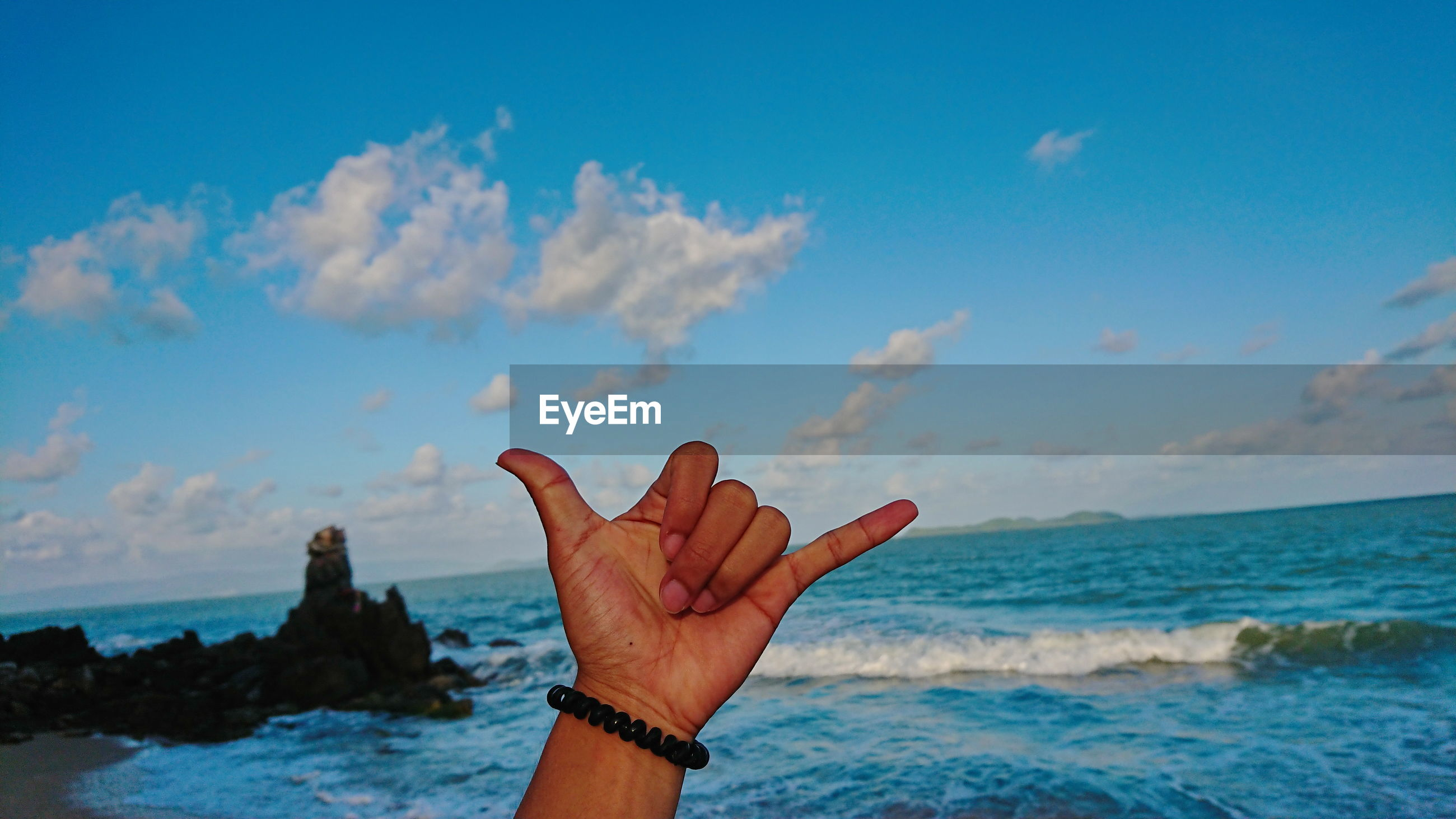 Cropped image of person gesturing by sea against sky