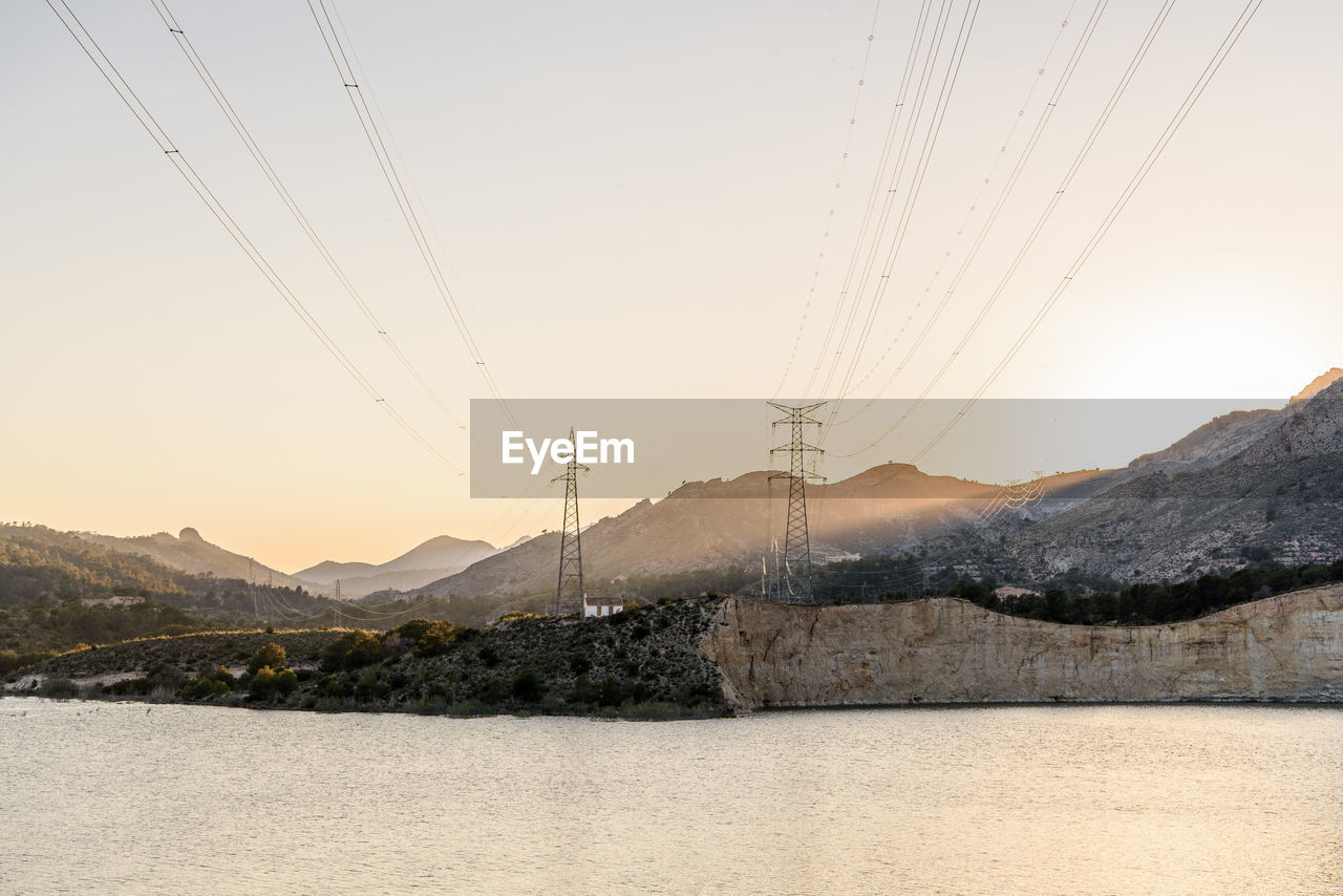 Scenic view of lake and mountains with electricity pylons against sky during sunset
