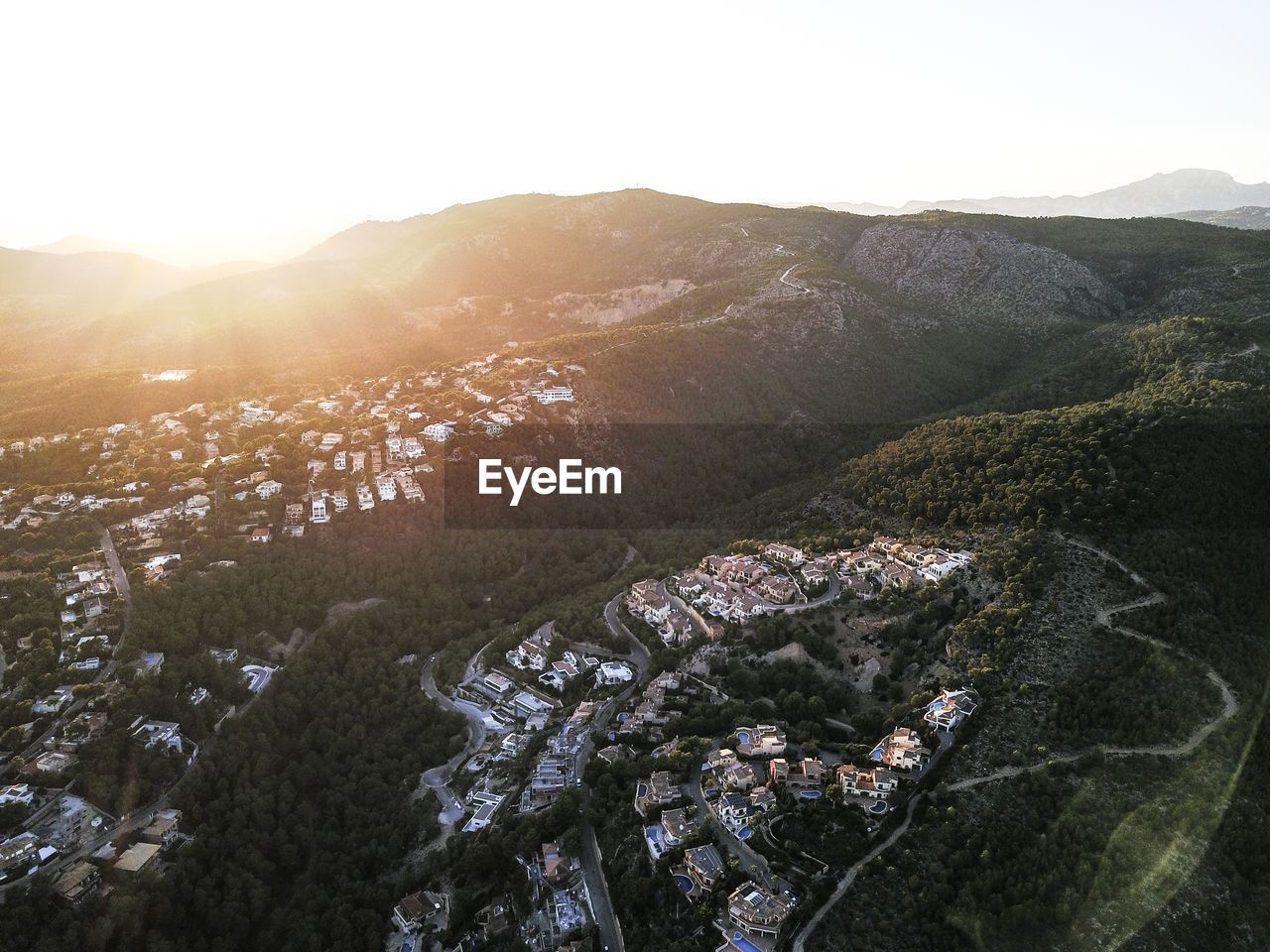High Angle View Of Houses On Mountains Against Sky During Sunset