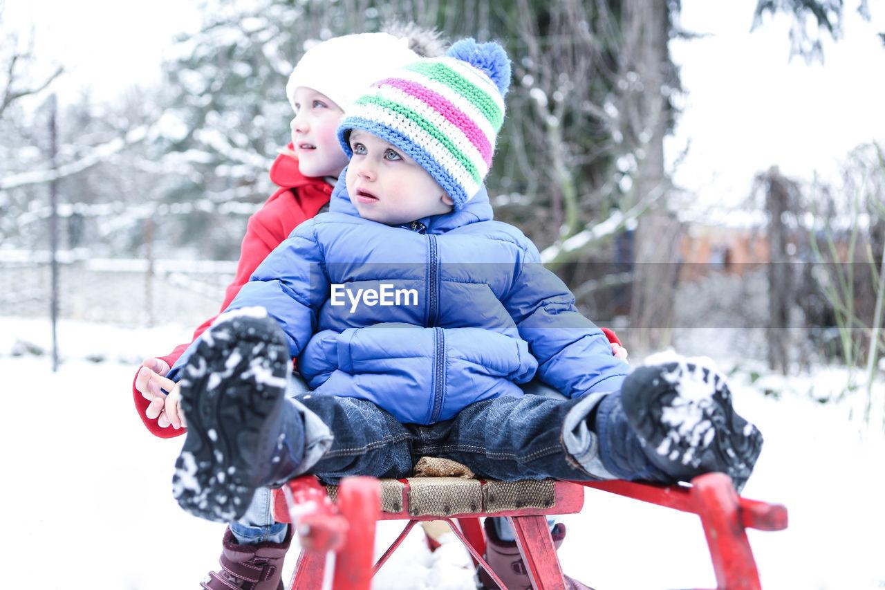 Cute siblings sitting on sled during winter