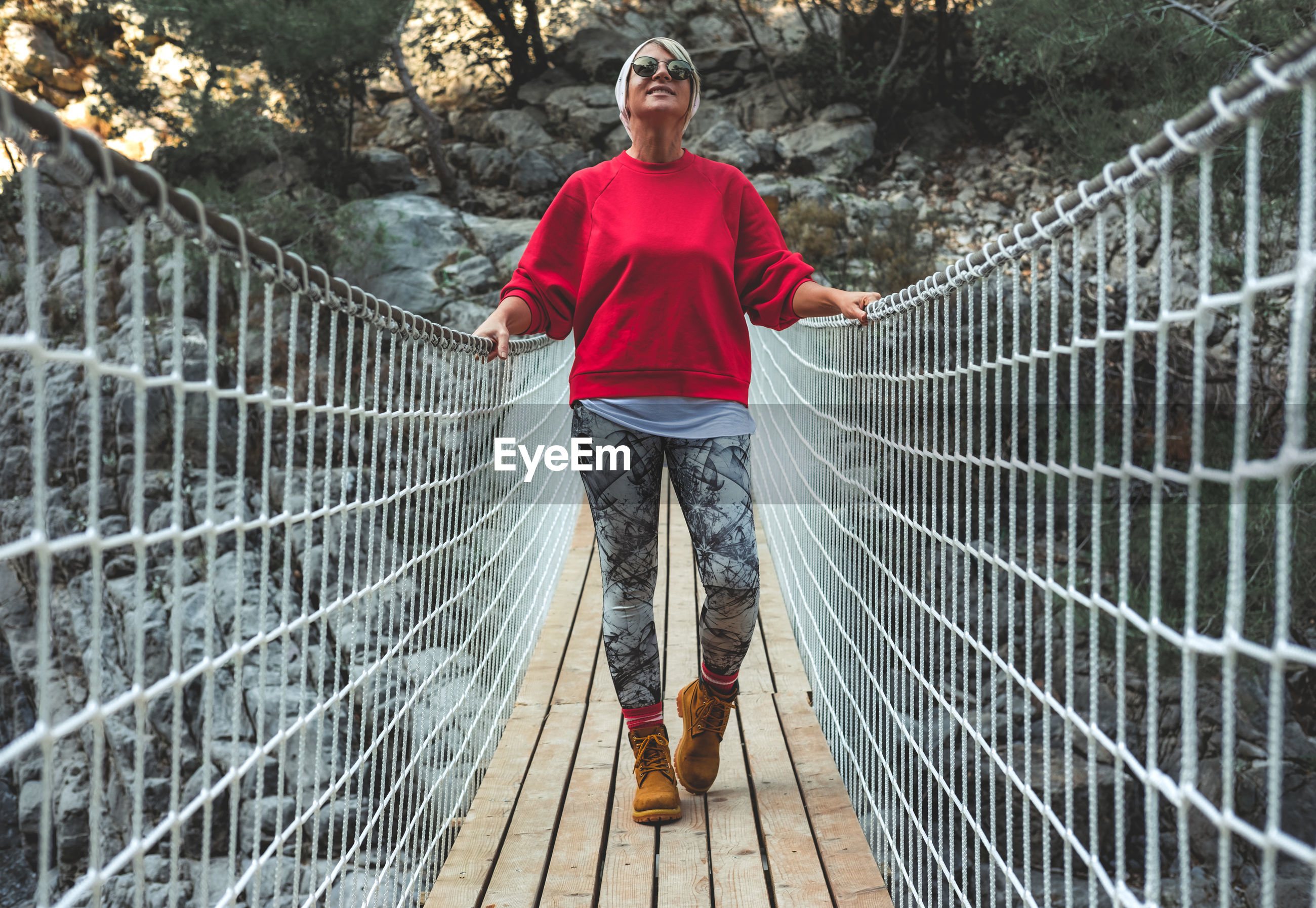 Adult woman standing on a hanging wooden bridge in the nature. goynuk kanyonu in antalya,turkey.