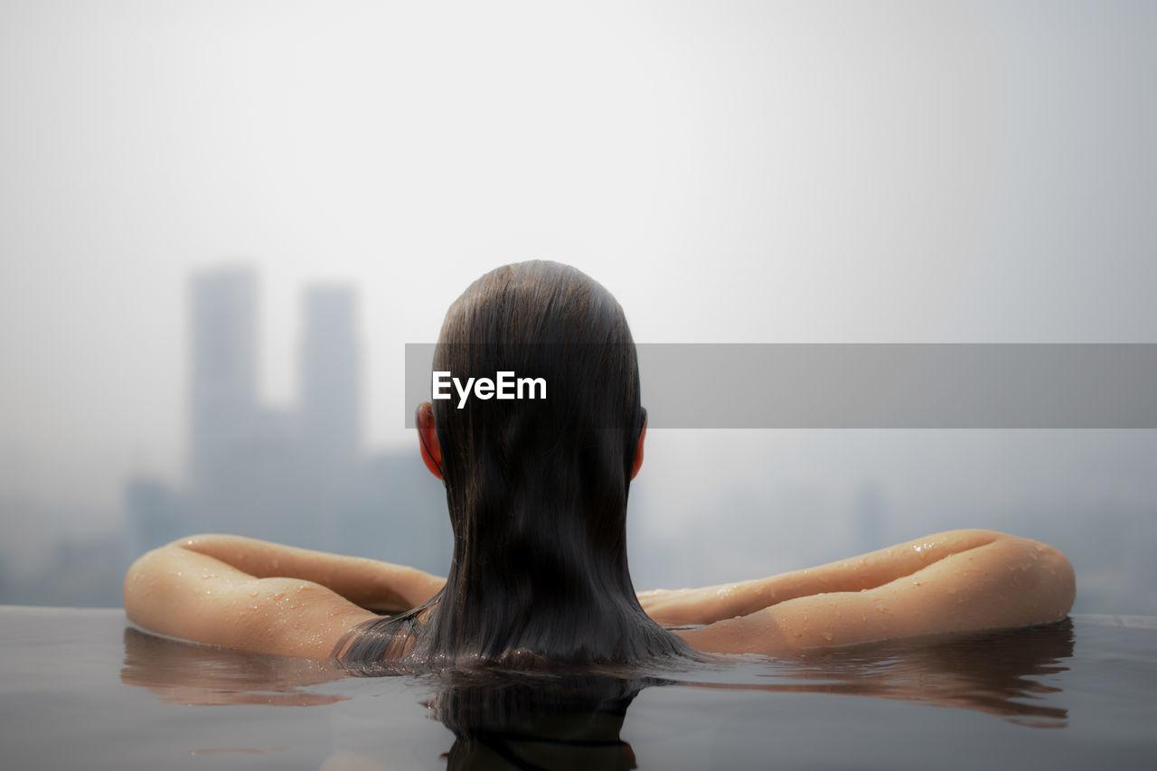 Rear view of woman in infinity pool against skyscrapers