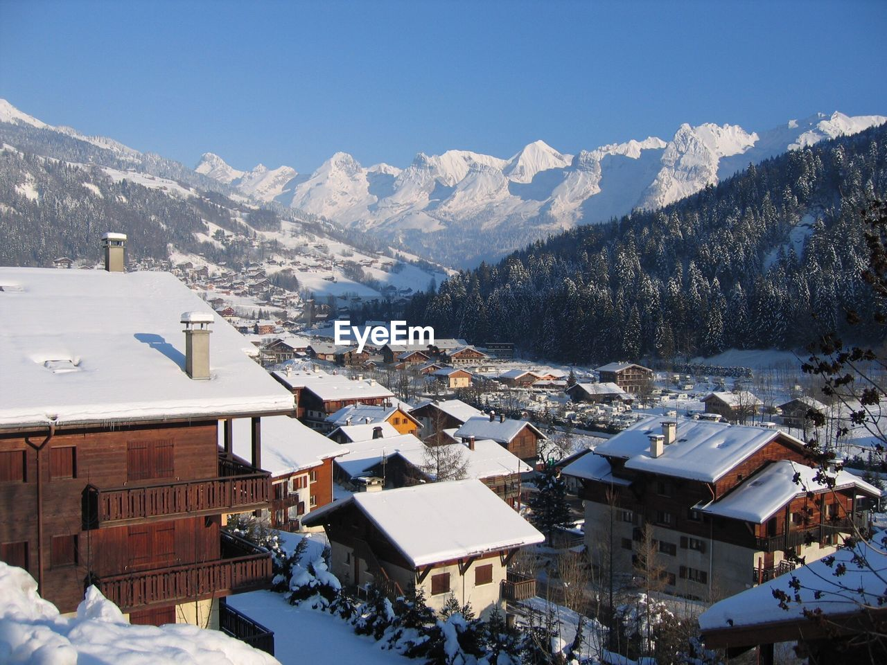 High Angle View Of Snow Covered Houses Against Blue Sky