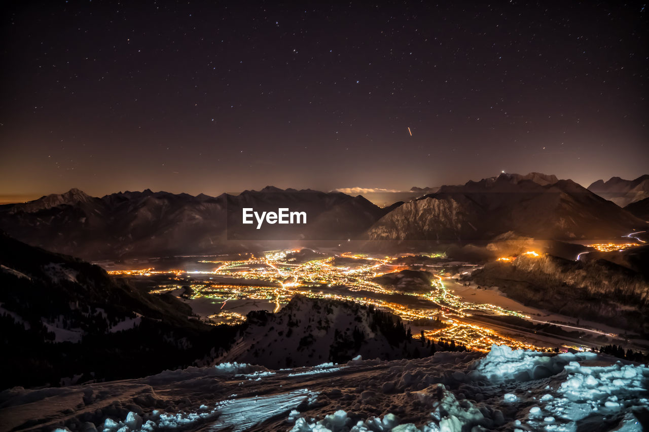 Aerial View Of Illuminated Snowcapped Mountains Against Sky At Night