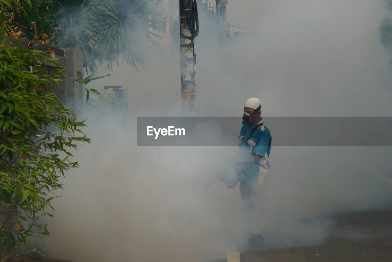 smoke - physical structure, real people, helmet, danger, protective workwear, firefighter, steam, headwear, outdoors, men, spraying, day, standing, one person, risk, working, nature, occupation, water, forest fire, hot spring, people
