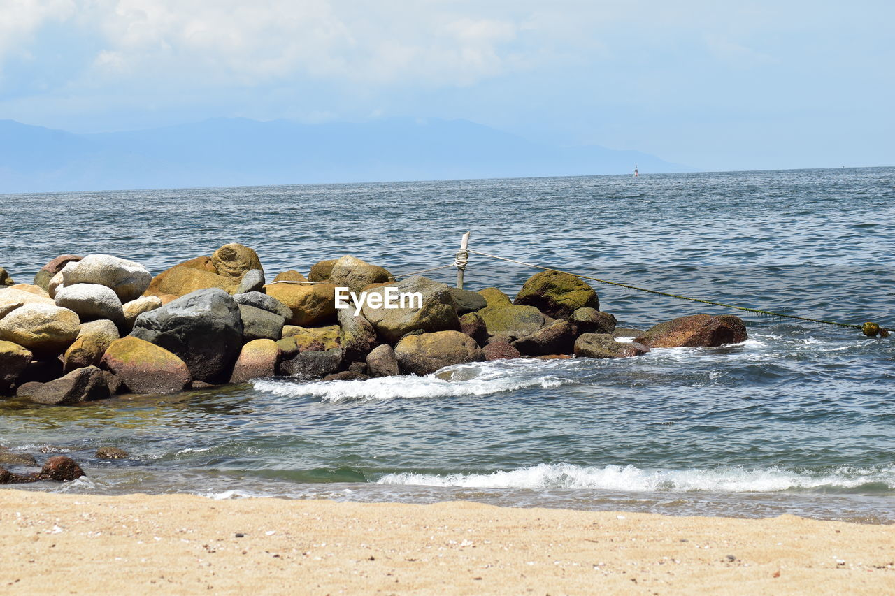 sea, water, beach, sky, land, scenics - nature, beauty in nature, rock, horizon, horizon over water, solid, rock - object, nature, motion, wave, day, tranquil scene, no people, tranquility, outdoors, groyne