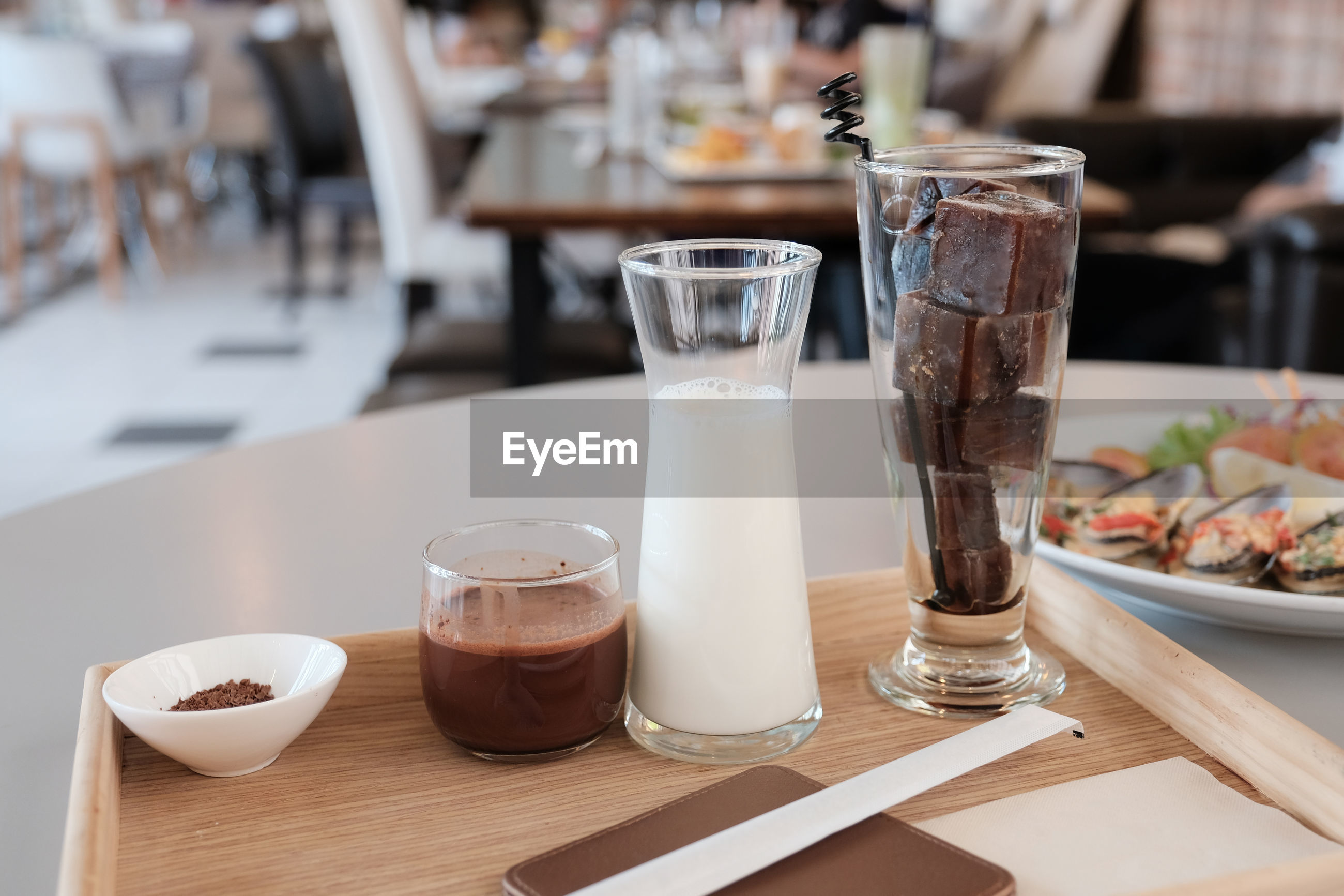 Close-up of milk and coffee with dessert on table in restaurant