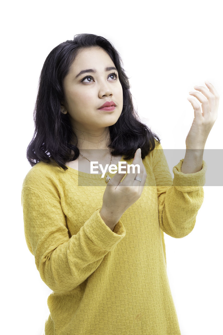 Young woman looking away standing against white background