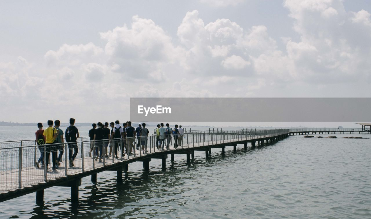 People standing on pier over sea against sky