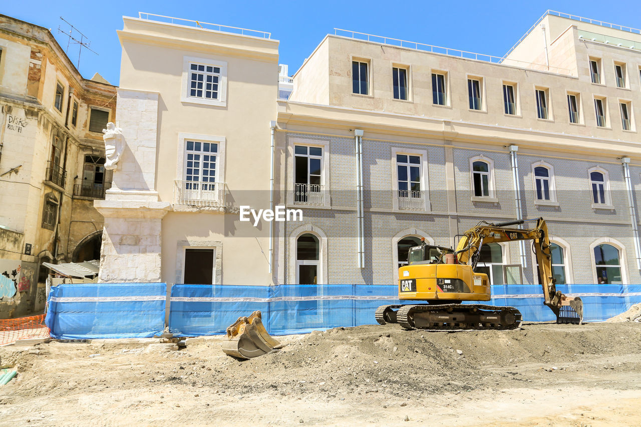 construction site, building exterior, built structure, construction machinery, architecture, earth mover, window, building - activity, land vehicle, machinery, day, no people, outdoors, industry, sky