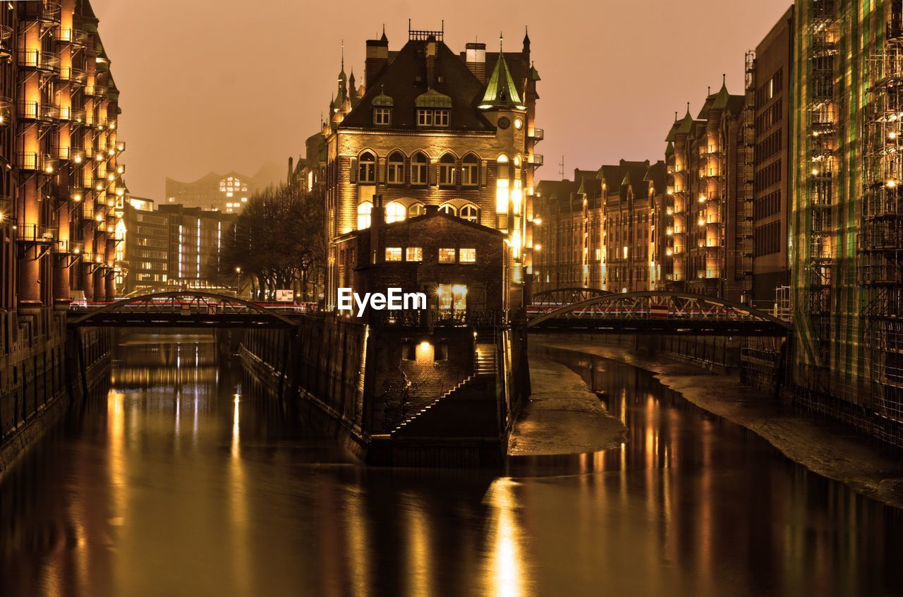 Bridge Over River Amidst Buildings In City At Night