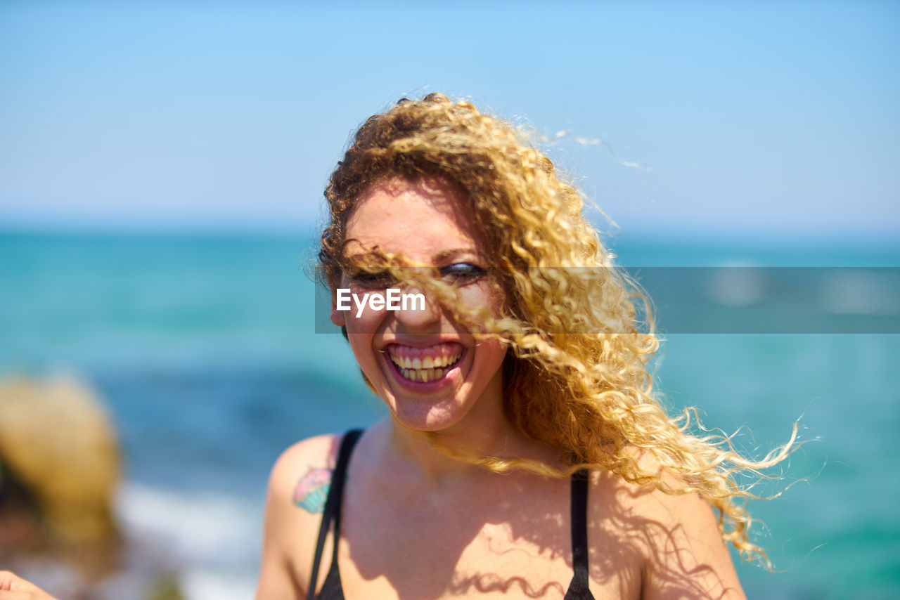 smiling, portrait, sea, happiness, hair, emotion, looking at camera, water, headshot, one person, toothy smile, beach, adult, teeth, leisure activity, hairstyle, cheerful, curly hair, focus on foreground, horizon over water, outdoors, beautiful woman