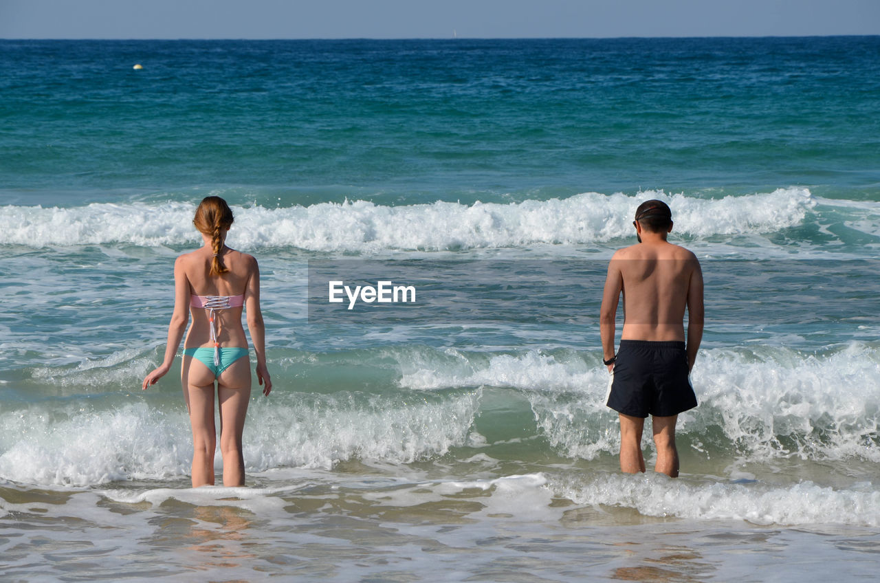 Rear view of man and woman standing in sea